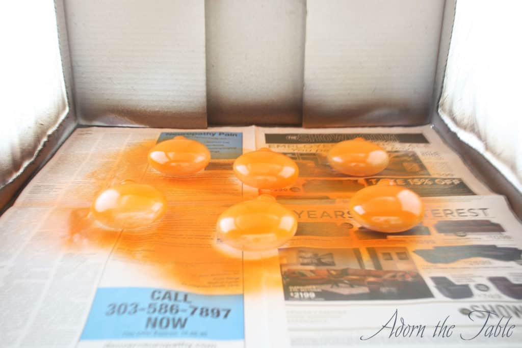 1st coat of orange spray paint on clear disc ornaments