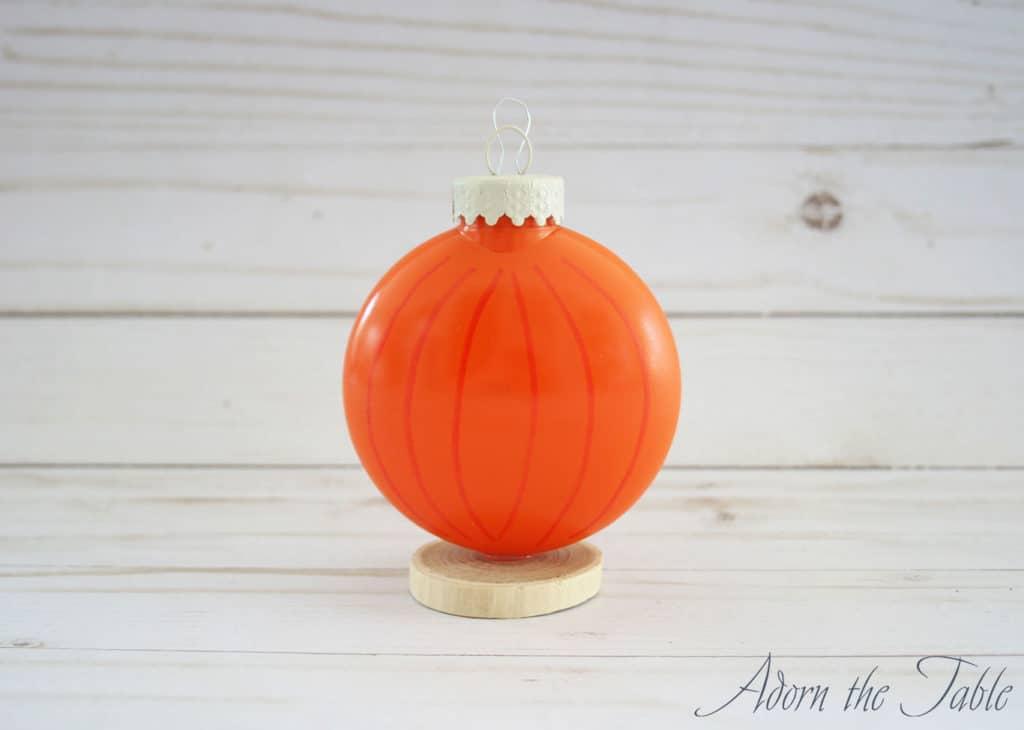 Orange pumpkin disc ornament added to wood piece